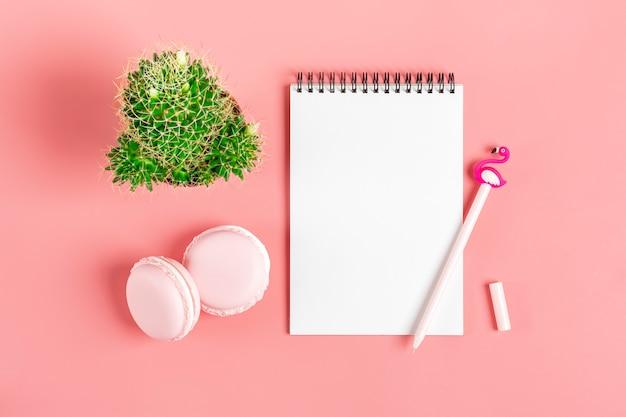 Weißes notizbuch für anmerkungen, makronen, stiftflamingo, hauptblumensucculent auf rosa hintergrund