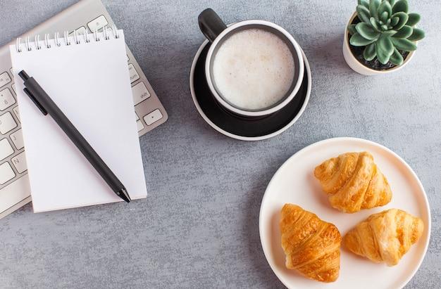 Weißes notizbuch, kaffee und croissant. leere seite des notizblocks zur eingabe von text. speicherplatz kopieren. lebensstil. hochwertiges foto