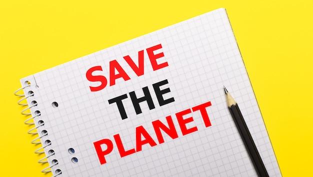 Weißes notizbuch mit der aufschrift save the planet mit schwarzem bleistift auf hellgelbem hintergrund.