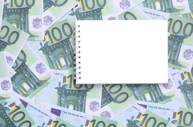 Weißes notizbuch mit sauberen seiten, die auf einem satz grüner währungsbezeichnungen von 100 euro liegen