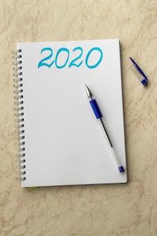 Weißes notizbuch und die blaue aufschrift 2020. blauer stift auf papier und kappe auf einer tabelle