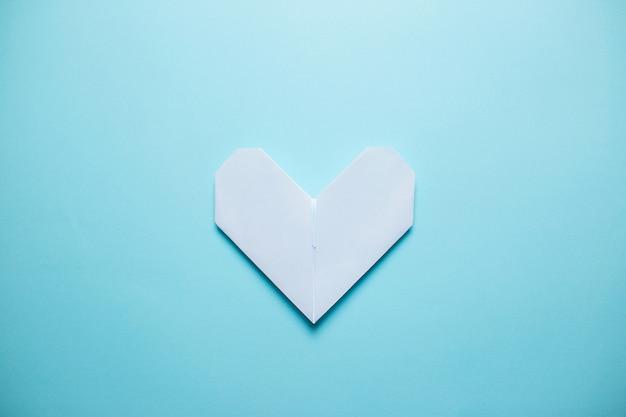 Weißes origamiherz auf blauem hintergrund. valentinstagkarte auf blauem hintergrund.