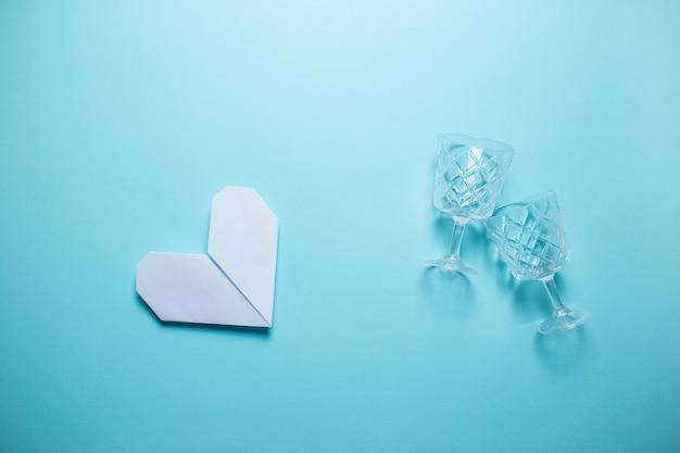 Weißes origamiherz mit weingläsern auf blauem hintergrund. valentinstagkarte auf blauem hintergrund.
