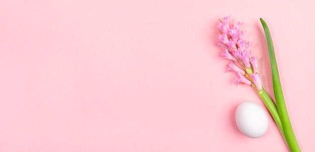 Weißes osterei und rosa hyazinthenblume auf pastellrosa