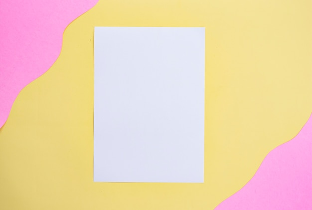 Weißes papier auf gelbem und rosa hintergrund. minimalistischer stil
