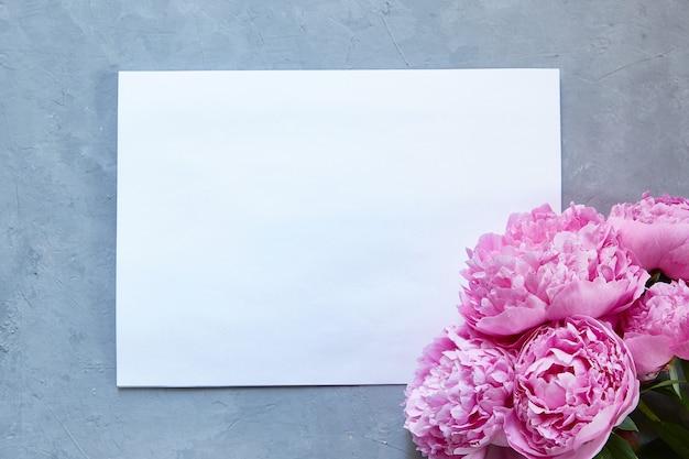 Weißes papier auf grauem hintergrund und ein strauß rosa pfingstrosen. speicherplatz kopieren