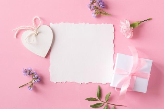 Weißes papier, blumen und hölzernes herz auf rosa hintergrund. draufsicht, flacher laienstil.