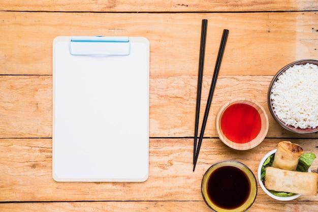 Weißes papier in der zwischenablage in der nähe der essstäbchen; frühlingsrollen; reis und saucen auf schreibtisch aus holz