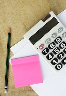 Weißes papier mit taschenrechner bleistift und notiz auf holz tisch
