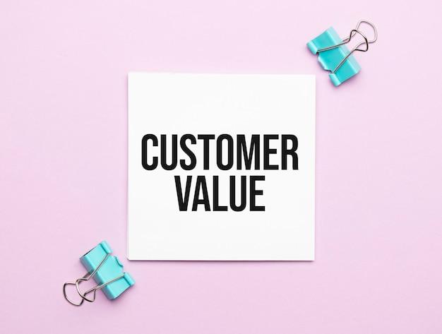 Weißes papier mit text kundenwert auf rosa hintergrund mit briefpapier