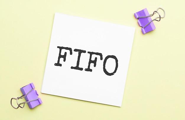 Weißes papier mit textfifo auf gelbem hintergrund mit briefpapier