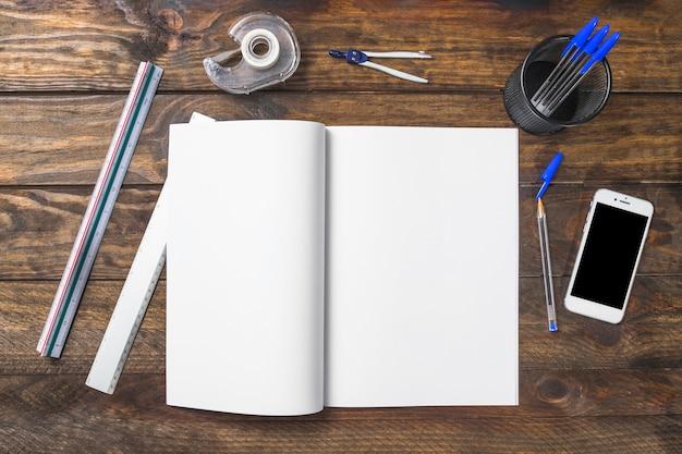Weißes papier umgeben mit schreibwaren und mobiltelefon