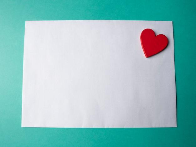 Weißes papier und ein roter herd auf einem grünen hintergrund. eine vorlage für ihr projekt zum valentinstag