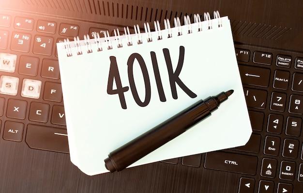 Weißes papierblatt mit text 401k auf dem schwarzen laptop