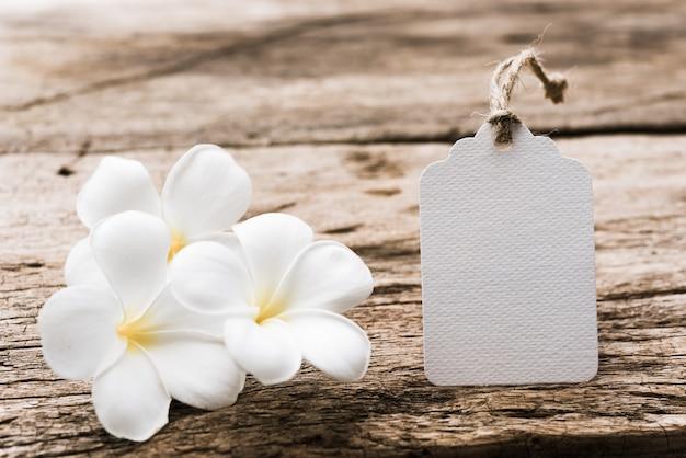 Weißes papieretikettenetikett verzieren mit plumeria-blumen auf rustikalem holztisch