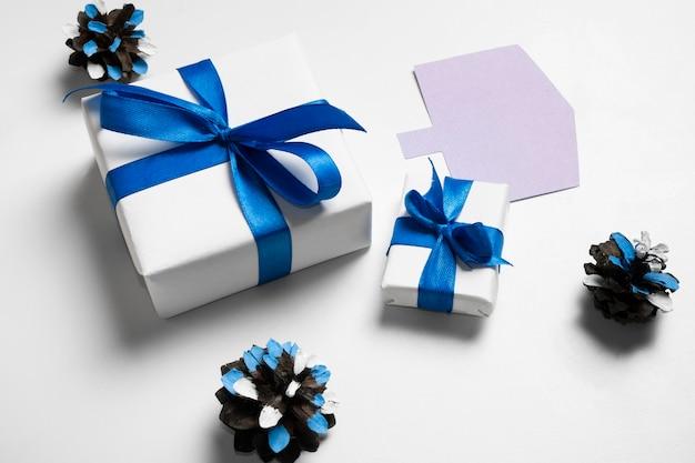 Weißes papiergeschenk der hohen ansicht und blaue bänder