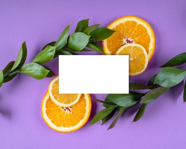 Weißes papierkartennotiz helles blumenblatt und orange fruchtzusammensetzungsmodellgrußkartenkopie