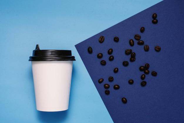 Weißes pappglas mit einem schwarzen plastikdeckel auf einer blauen und cyan-blauen oberfläche mit kaffeebohnen. glas mit kaffee zum mitnehmen. die trendfarbe ist klassisches blau. exemplar, flach zu legen