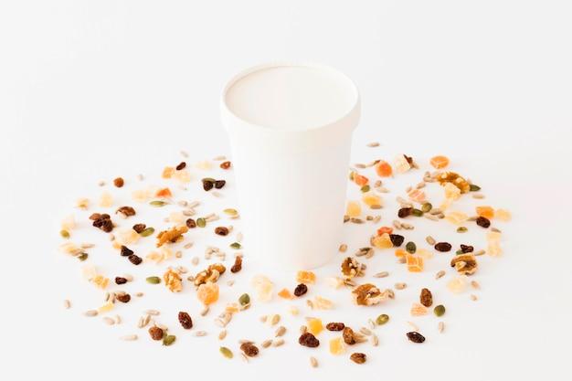 Weißes pappglas zwischen getrockneten früchten und nüssen