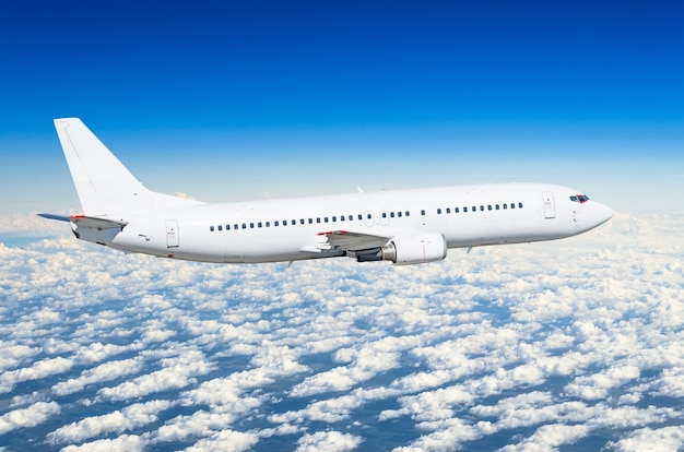 Weißes passagierflugzeug auf der seitenansicht, fliegt auf einem flughöhe.