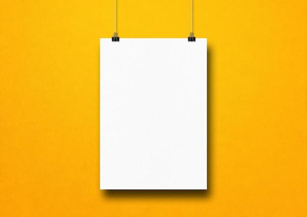 Weißes plakat, das an einer gelben wand mit clips hängt. leere modellvorlage