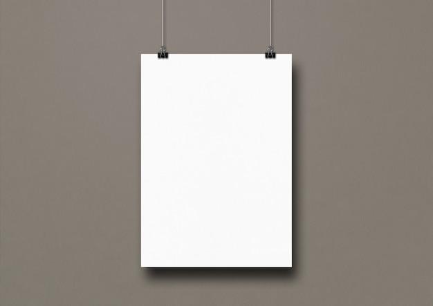 Weißes plakat, das an einer grauen wand mit clips hängt.