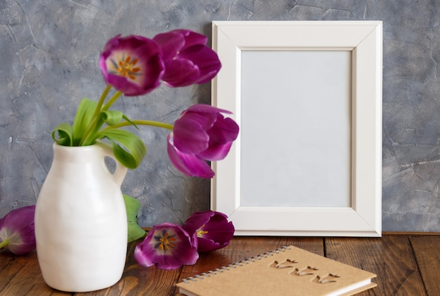 Weißes plakatrahmenmodell mit lila tulpen in einer vase nahe der grauen wand