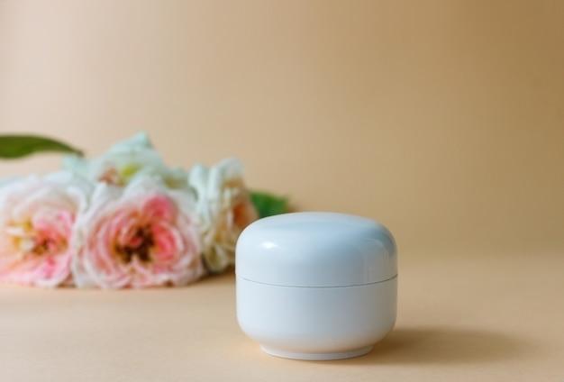 Weißes plastikglas feuchtigkeitscreme auf einem hintergrund von beige rosen