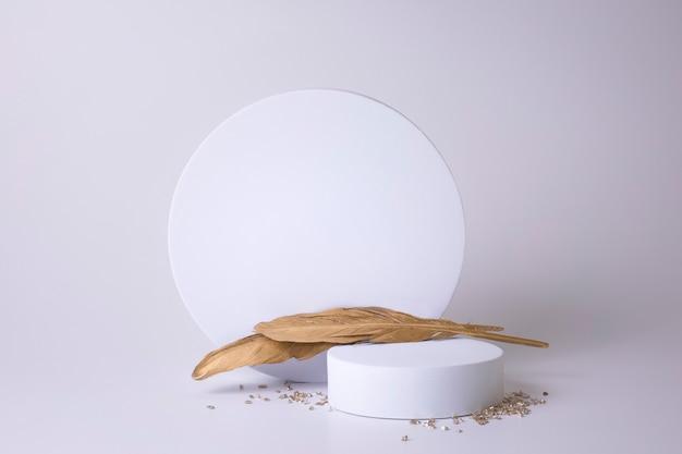 Weißes podest auf weißem hintergrund mit goldenen federn und kleinen kristallen. podium für produkt, kosmetische präsentation. kreatives mock-up. sockel oder plattform für schönheitsprodukte. minimalistisches design.