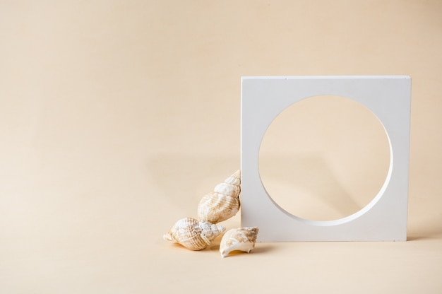 Weißes podium auf beigem hintergrund. vorlage, mock-up für präsentationsprodukte. pastellfarben gestaltete komposition mit natürlichen muscheln und geometrischen formen. minimales konzept. produktmodell.