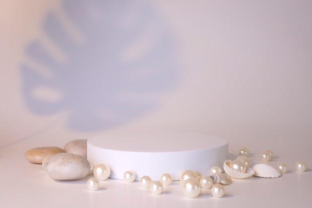 Weißes podium auf weißem hintergrund mit perlen und muscheln. podium für produkt, kosmetische präsentation. kreatives mock-up. sockel oder plattform für schönheitsprodukte. minimalistisches design.