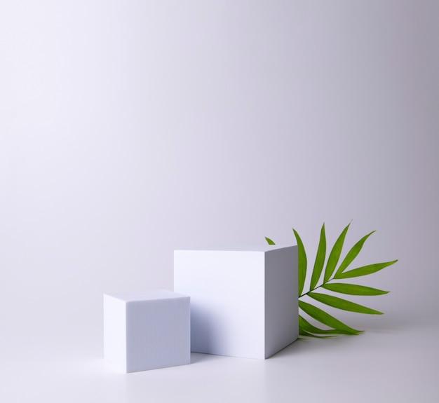 Weißes podium auf weißem hintergrund mit tropischem blatt podium für die produktkosmetikpräsentation