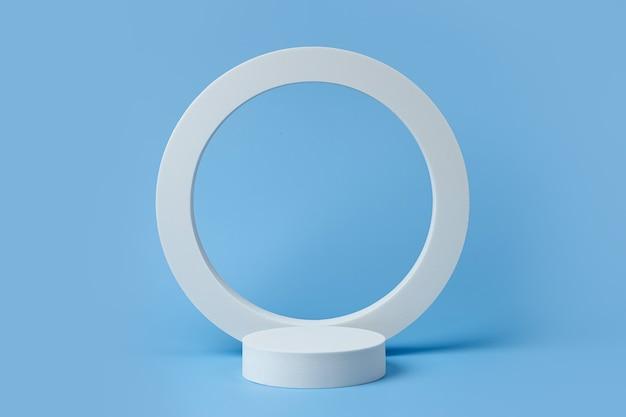 Weißes podium zur präsentation von kosmetikprodukten mit geometrischen formen auf blauem hintergrund