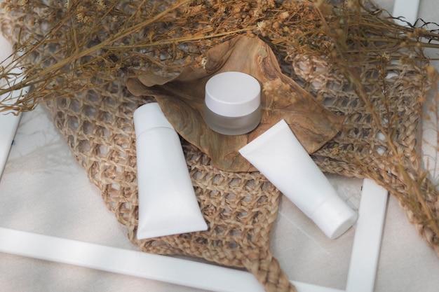 Weißes produkt der kosmetischen flaschenbehälter mit gesponnenen handtaschen, trockene blume, blatt.