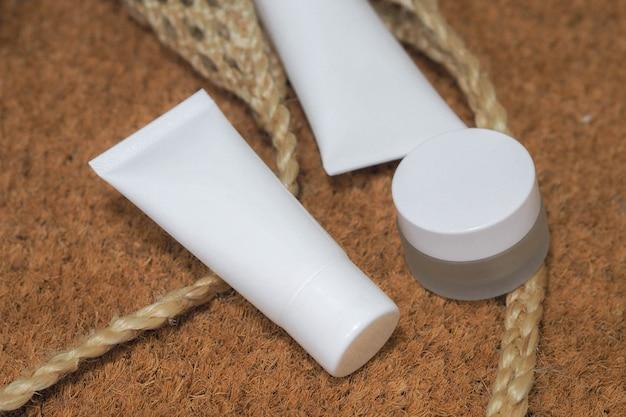 Weißes produkt der kosmetischen flaschenbehälter mit gesponnenen handtaschen.