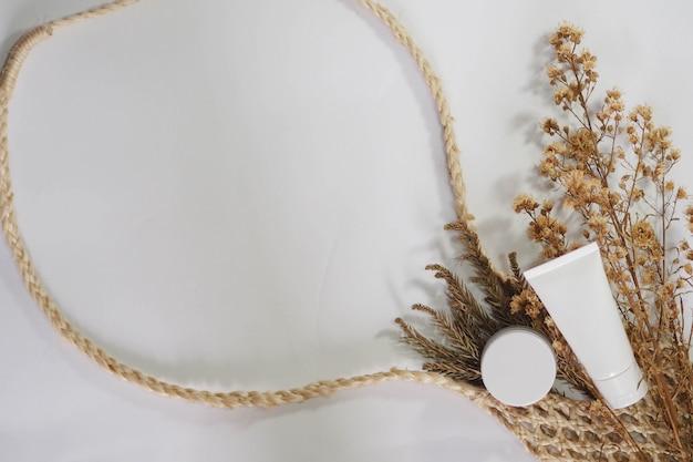 Weißes produkt der kosmetischen flaschenbehälter mit trockener blume und gesponnenen handtaschen.