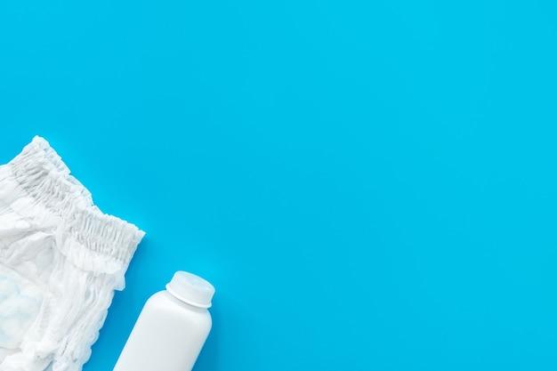 Weißes pulver, windel auf blauem hintergrund, flatley, draufsicht, kopierraum, mock-up. babyhygiene, hintergrund für neugeborene jungen.