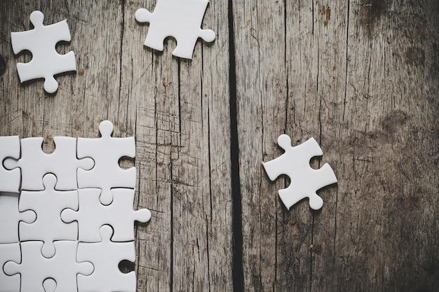 Weißes puzzle auf einem holztisch