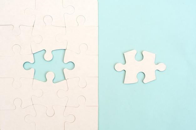 Weißes puzzle auf einer draufsicht des blauen hintergrunds.