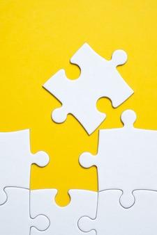 Weißes puzzle aus fast allen details gefaltet. der begriff der vollständigkeit.