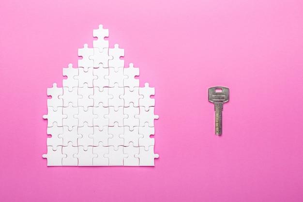Weißes puzzle. hausform puzzle und schlüssel. das konzept der miete, hypothek. ansicht von oben