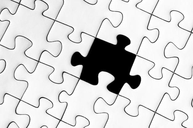 Weißes puzzle mit einem fehlenden schwarzen teil - vervollständige das missionskonzept