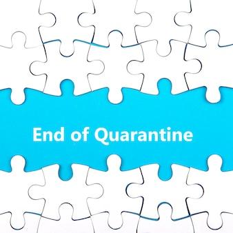 Weißes puzzle mit fehlenden teilen. wörter ende der quarantine. ende des coronavirus- und quarantänekonzepts