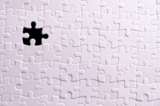 Weißes puzzle und ein fehlendes puzzleteil.