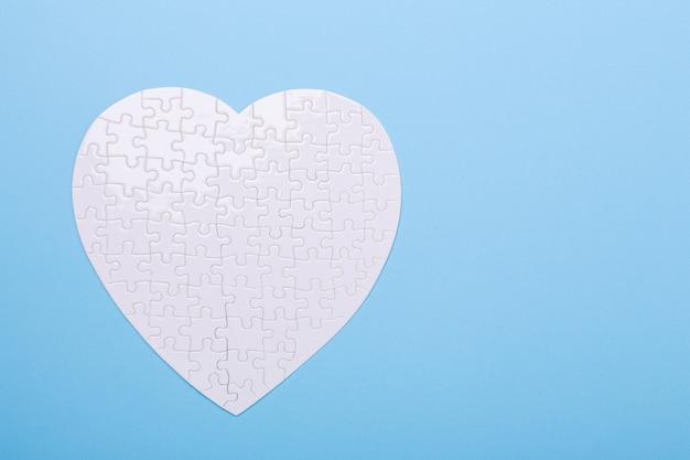 Weißes puzzlespiel in form des herzens auf blau