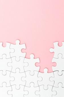 Weißes puzzlespiel über rosa hintergrund mit fehlenden stücken. unvollständige elemente, lösungssuchkonzept