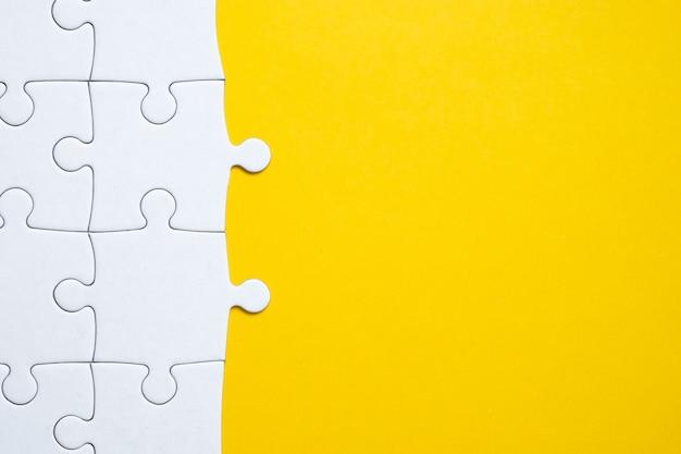 Weißes puzzlespiel zusammengebaut zur hälfte auf einem gelben hintergrund. kopieren sie platz.