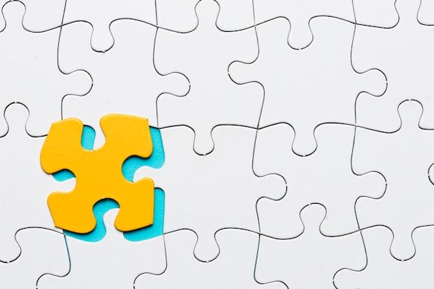 Weißes puzzlespielgitter mit gelbem puzzlespielstückhintergrund