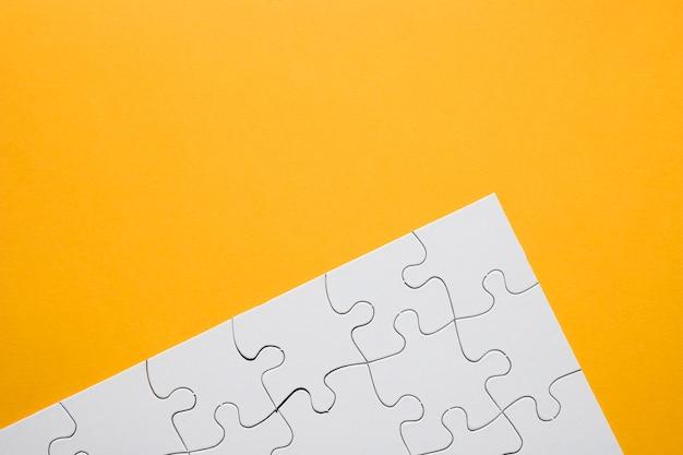 Weißes puzzlespielgitter über gelbem hintergrund