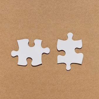 Weißes puzzlestück über strukturiertem hintergrund des braunen papiers